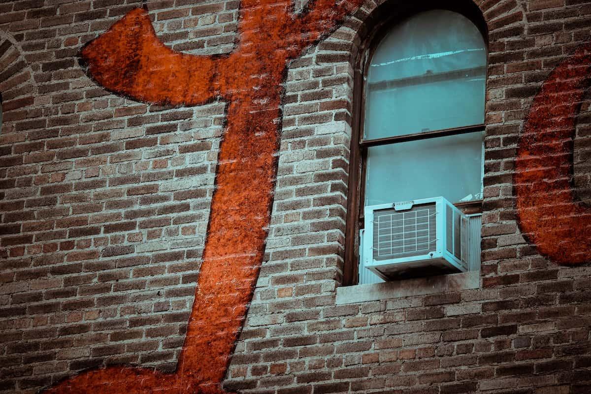 AC unit in a window against a brick wall