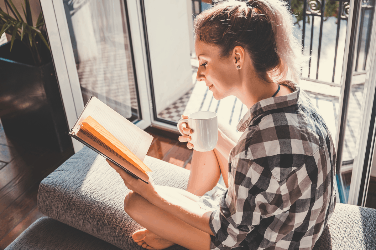 Woman reading a book and drinking coffee.